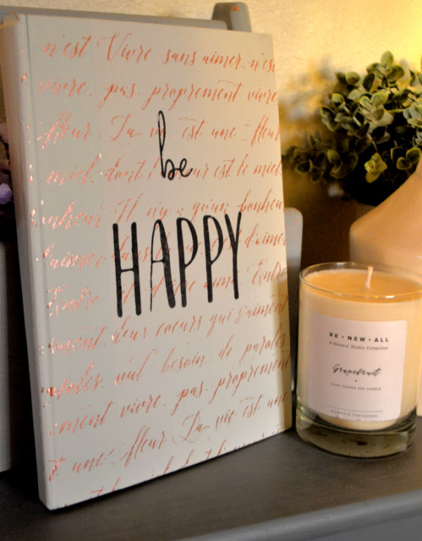 A white painted book with copper french script and the words be happy in black over top