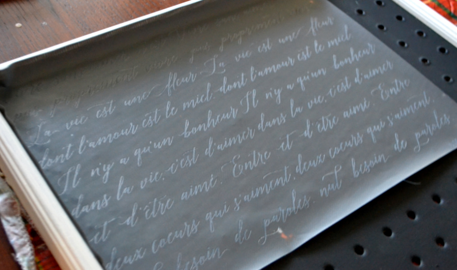 A french script mesh stencil laying on a black painted pegboard