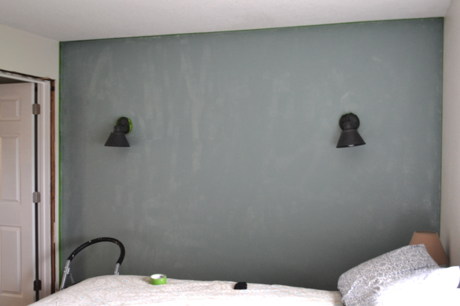A teal wall with a bed in the foreground and two black sconces on each side of the picture
