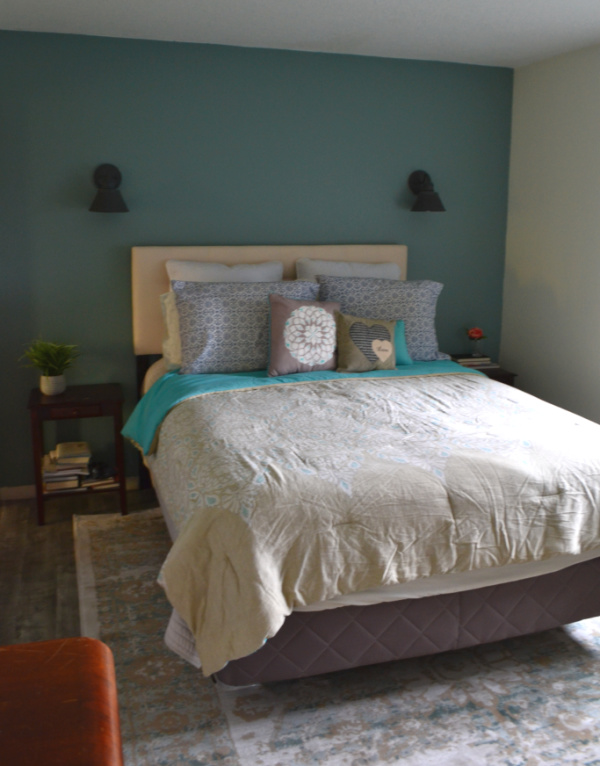 Queen size bed made up with lot of pillows against a blue/teal painted wall with sconces on either side of the bed with a blue/white rug beneath the bed