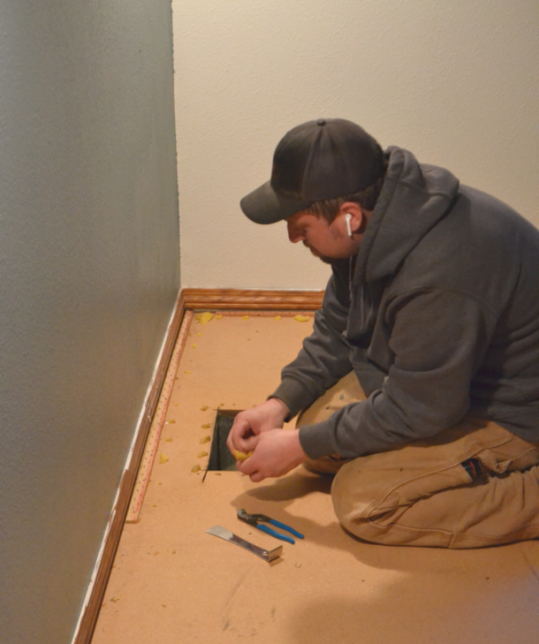 A man sitting on his knees on a floor near a heat vent with a screwdriver and pliers removing floor staples from a subfloor