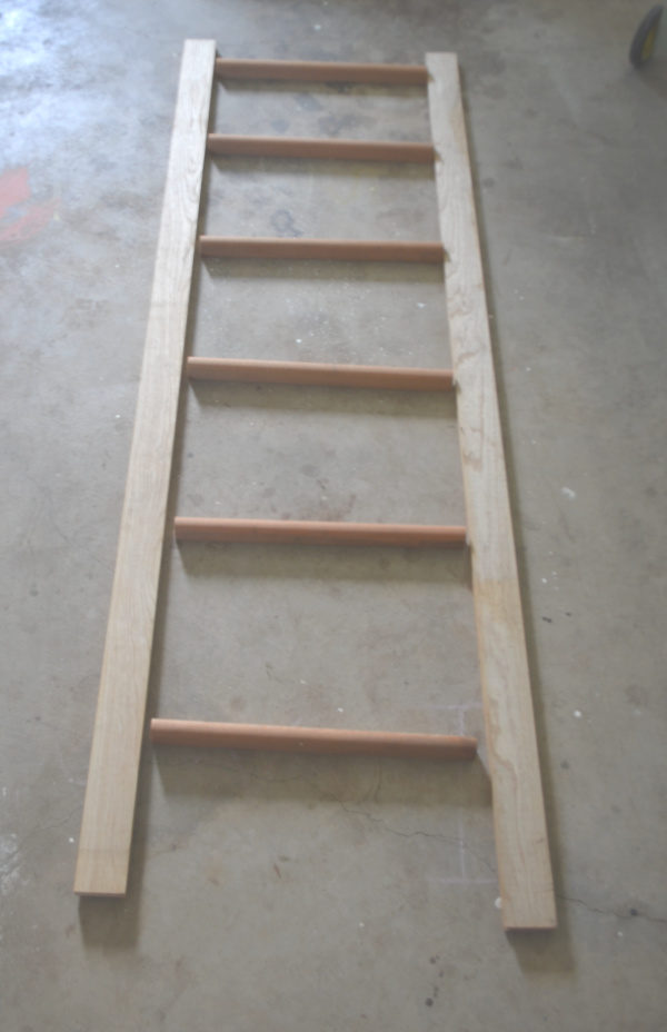 An above view of a ladder not assembled laying on a concrete floor