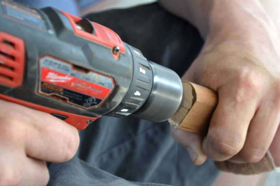 A close up view of a man's hands holding a drill and a ladder rung