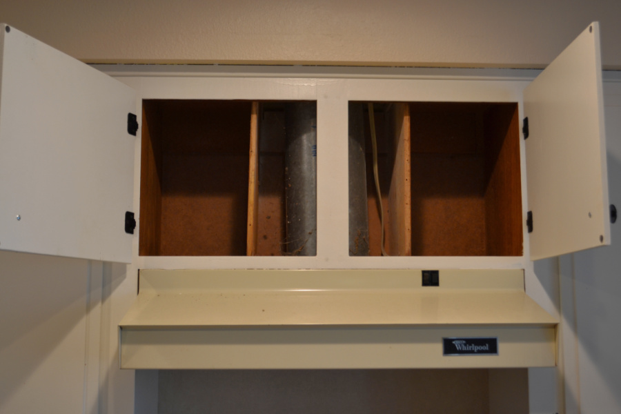 A front facing view of a range hood with upper white cabinets that are opened to reveal a venting pipe surrounded by wood