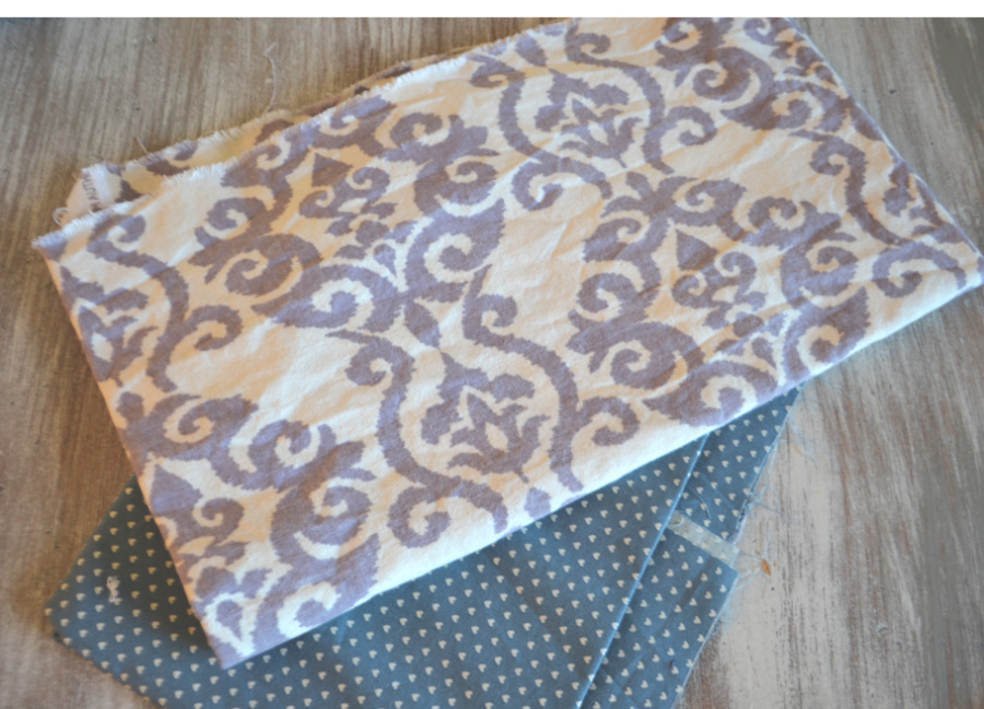 Blue fabric with tiny hearts and linen type fabric with purple design sitting on a whitewashed table