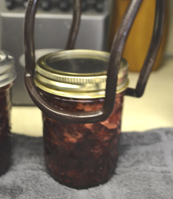 A sealed canning jar with a lid and canning ring around it being picked up by canning tongs