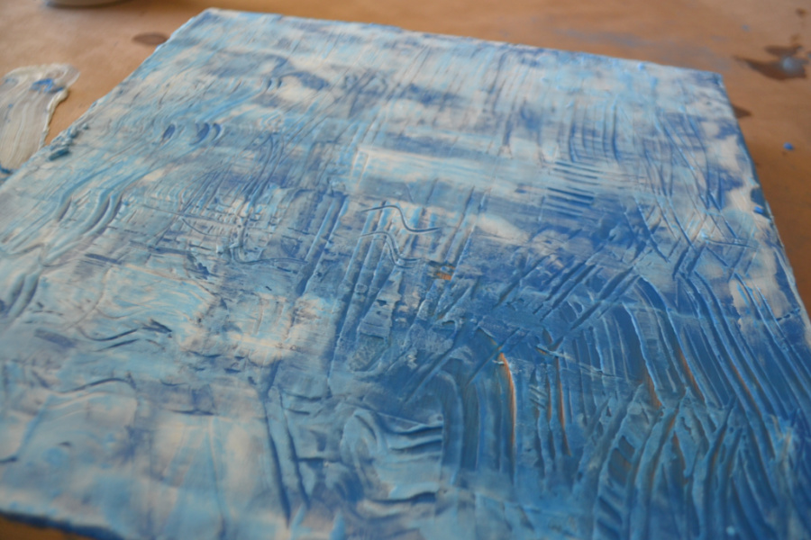 A close up photo of a blue and white wax surface with scraped markes over the entire surface in a random assortment