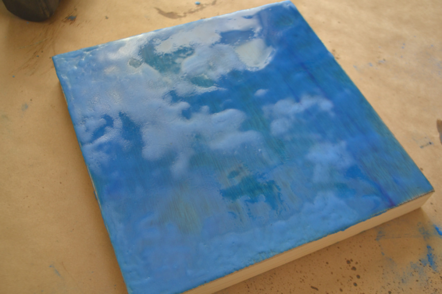 A blue wax painted surface sitting on a piece of brown paper