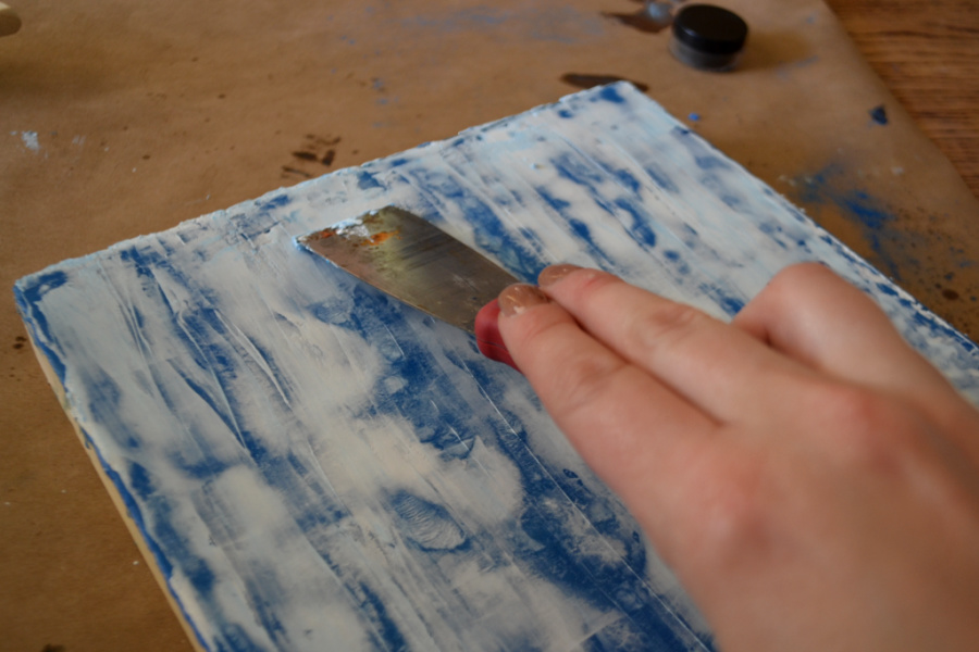 A putty knife being dragged across a surface covered with white and blue wax