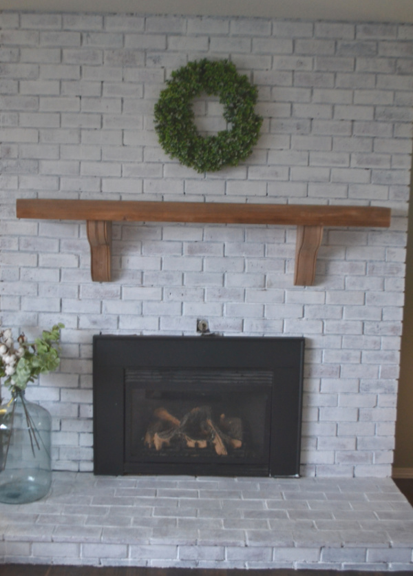A straight on view of a fireplace with a solid wood mantel with corbels attached