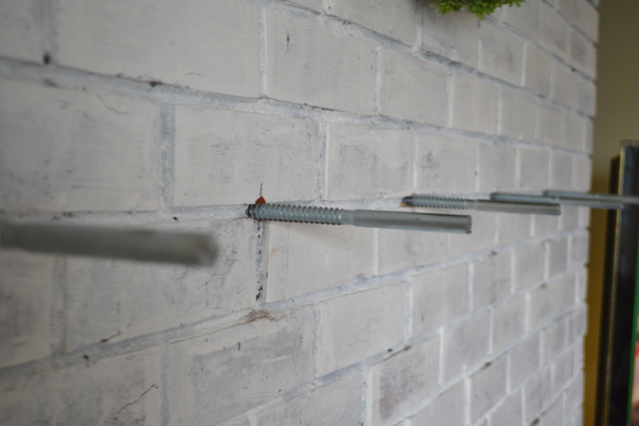 A side view of lag bolts sticking out of a brick fireplace with the heads of the bolts cut off