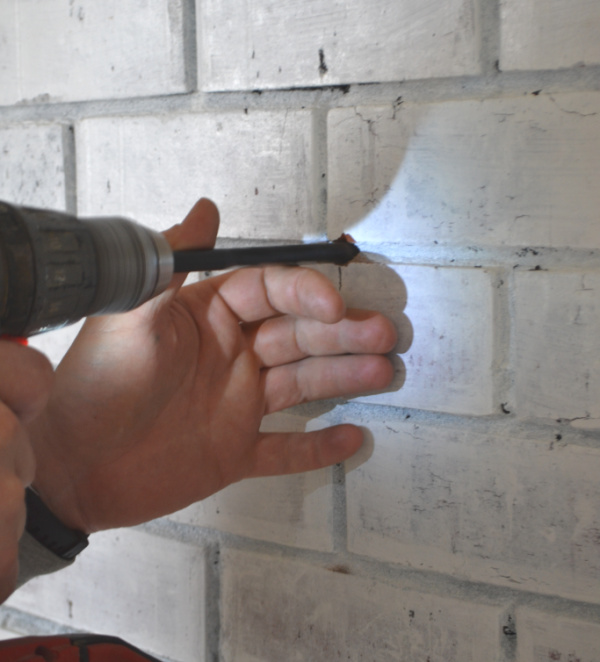 A whitewash brick fireplace up close with a mans hand guiding a drill into the brick