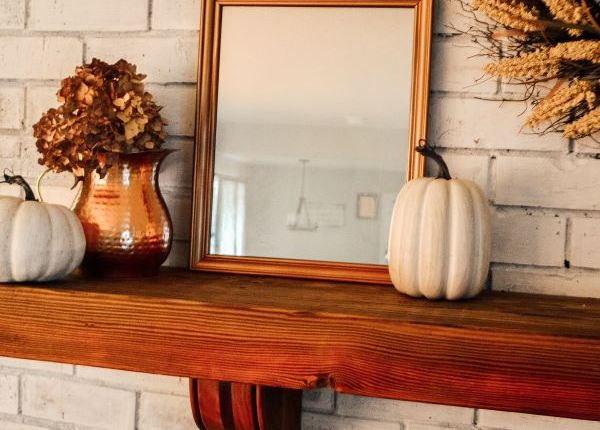 A white brick fireplace with a solid wood dark mantle with a copper framed mirror surrounded with white pumpkins and a copper pot