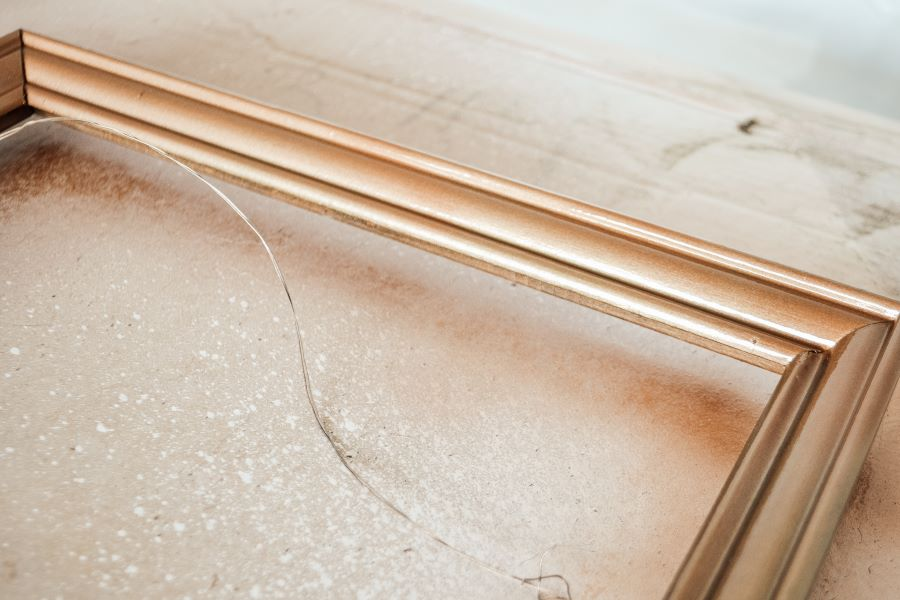 A close up of the edge of a picture frame that has been painted with copper spray paint
