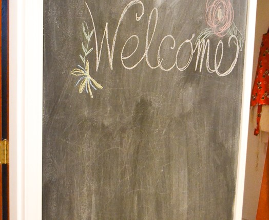 A wall between doorways is painted with black chalkboard paint, and a chalk writing of the word welcome on the wall