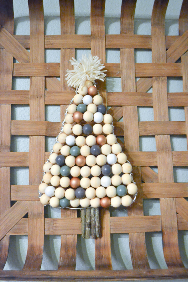 A completed wooden beaded Christmas tree with a yarn pom pom star and wooden sticks as the trunk
