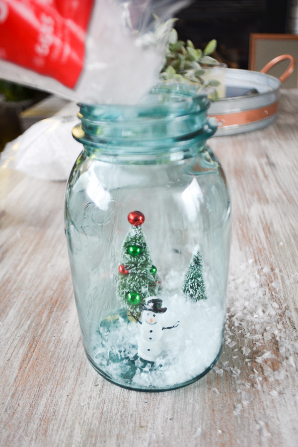 A blue mason jar sitting on a table with two bottle trees and a snowman on the bottom as fake snow is dumped from overhead