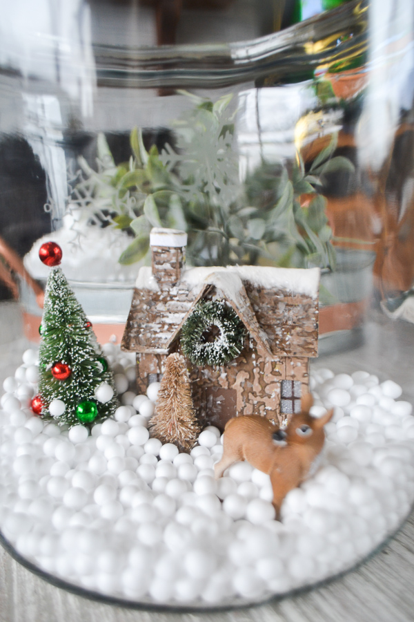 A clear glass container with a cabin, tree and deer surround by fake tiny snowballs