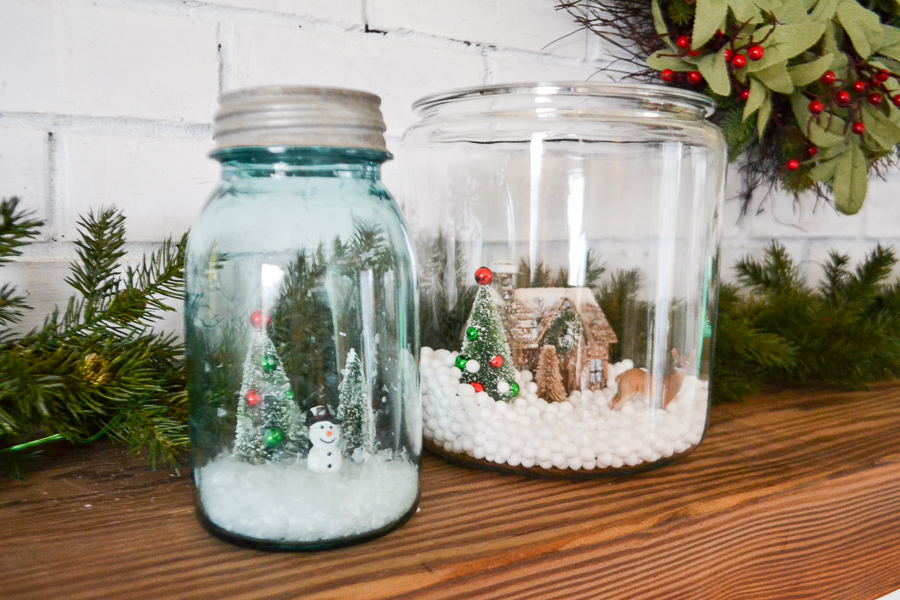 A vintage blue mason jar with a lid and an open large clear glass container with fake snow and a fake little christmas tree inside