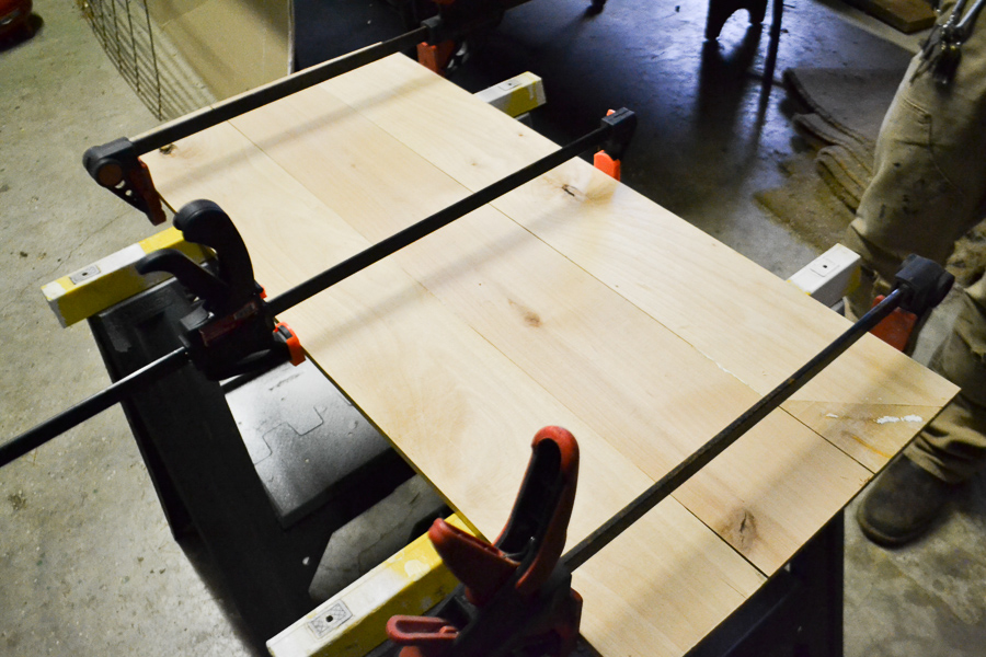 Three clamps holding boards in place that have been glued together