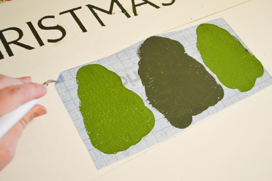 A close up of trees painted with a sponge waiting for the stencil to be removed