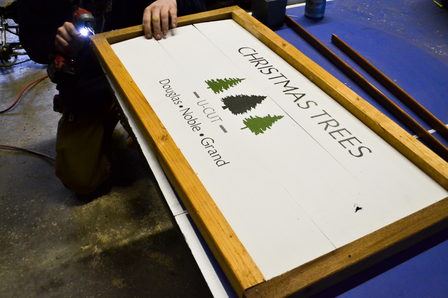 A Christmas tree wood sign sitting on a surface so that the wood frame can be attached