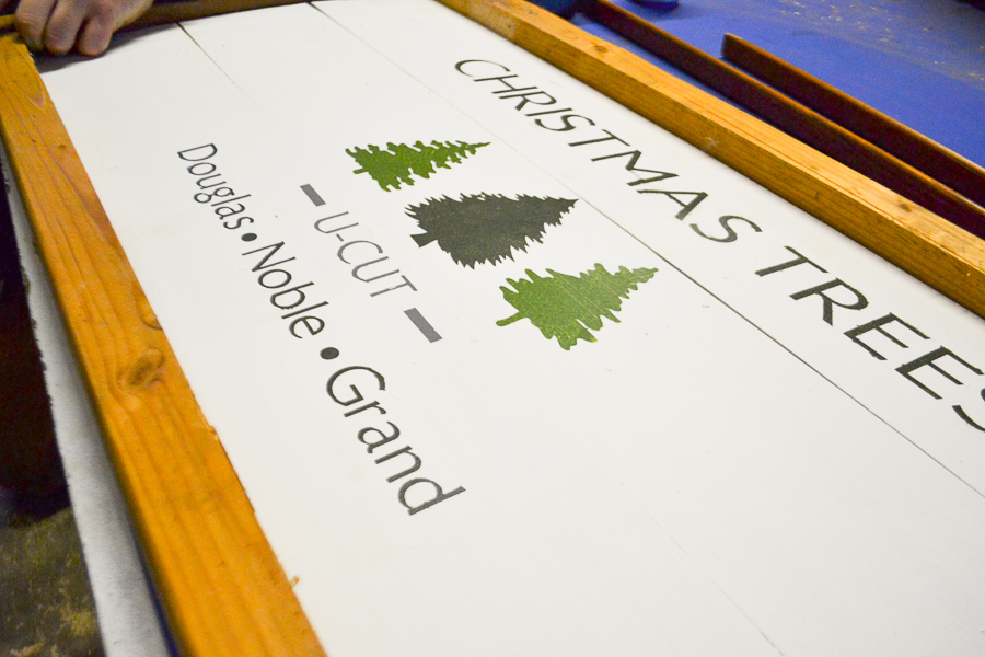 A close up of a white painted board with the word Christmas tree and trees painted in green