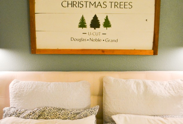 A Christmas tree painted wood sign hanging above a bed