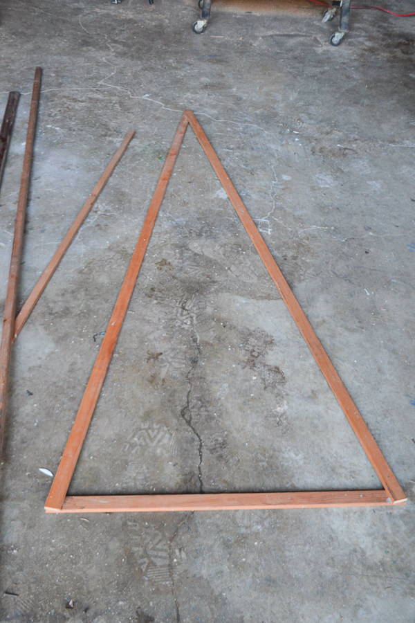 Wood trim in the shape of a triangle laying on a concrete floor