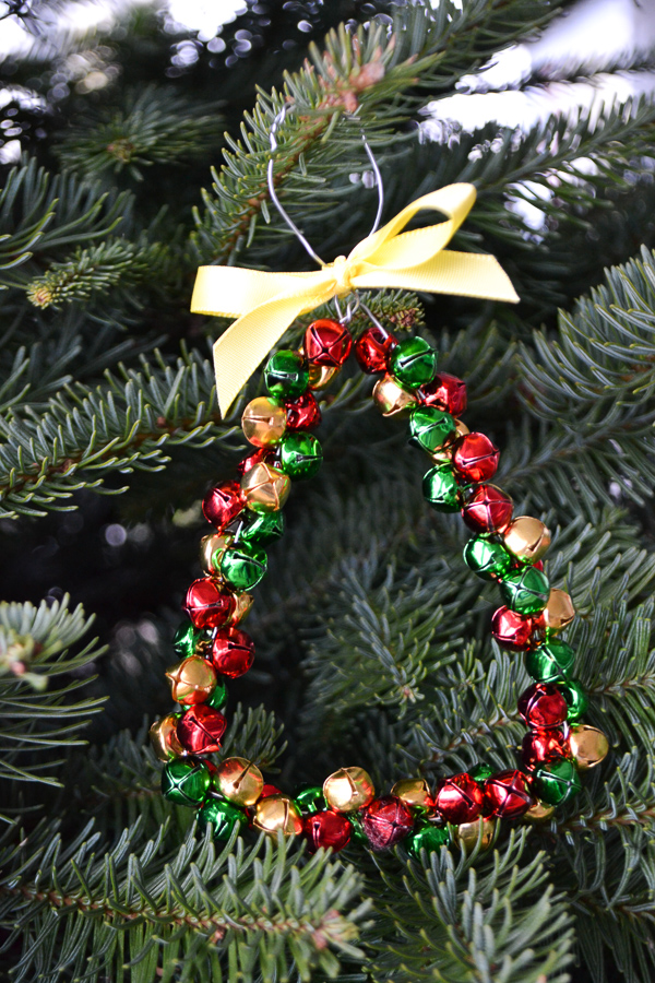 A triangle red, green, gold jingle bell ornament hanging on a tree with a yellow bow on top
