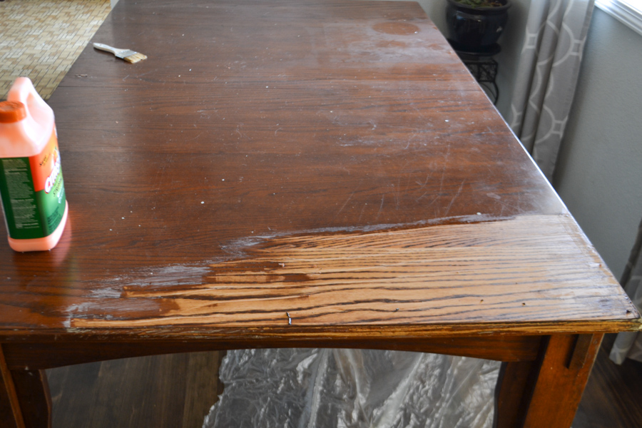 A close up of a table with some of the dark stain missing