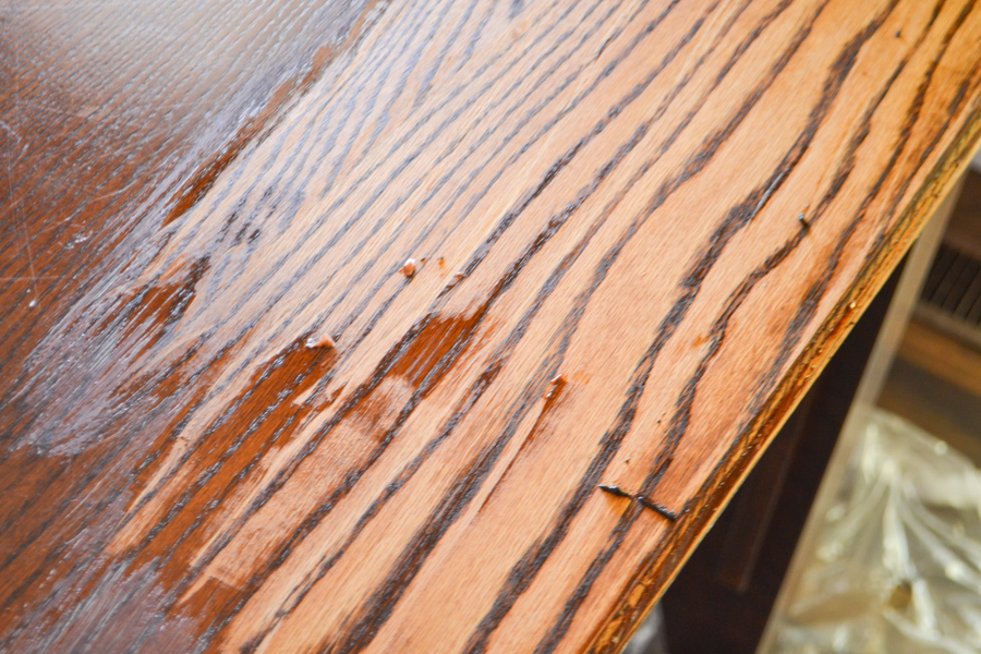 A close up picture of a tabletop that has half the stain stripped off