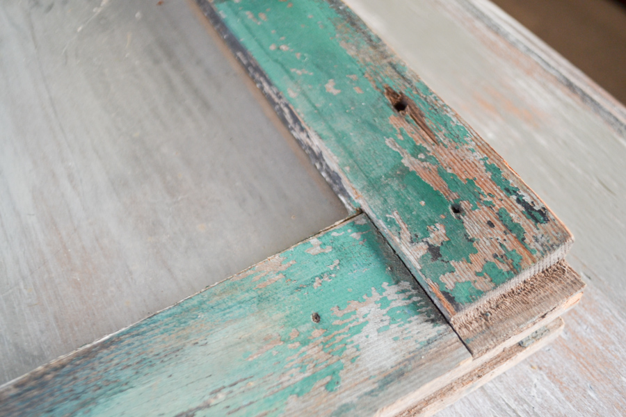 A close up picture of a vintage window with chippy green paint
