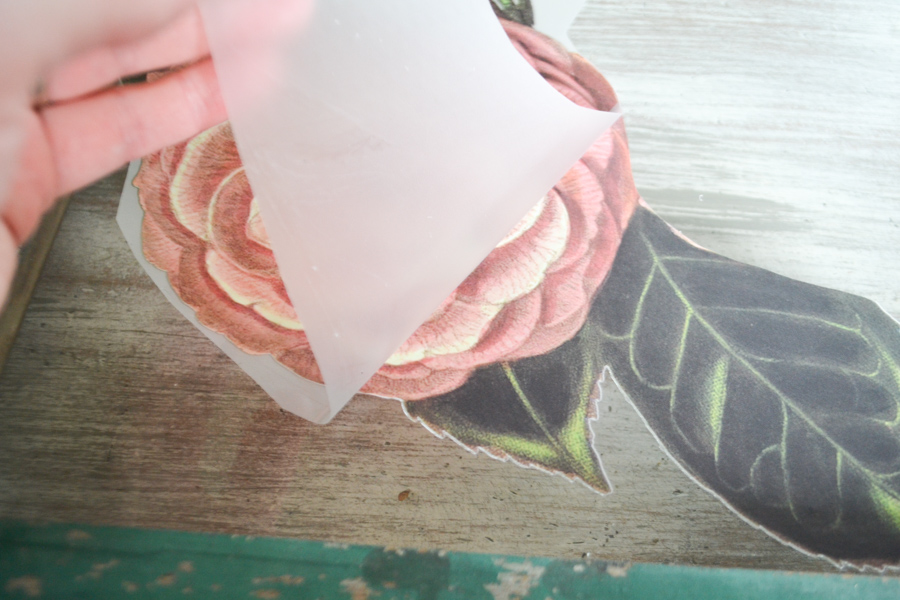 A close up picture of someone's hand removing transfer paper from an inked flower