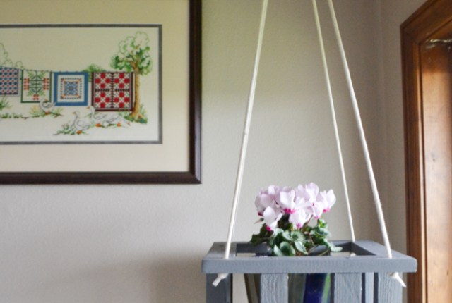 A gray wooden plant stand hanging from a ceiling with a cross stitched picture on the wall behind it and a window to the right