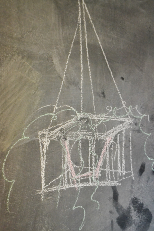 A chalk drawing of a rough sketch of a hanging plant stand