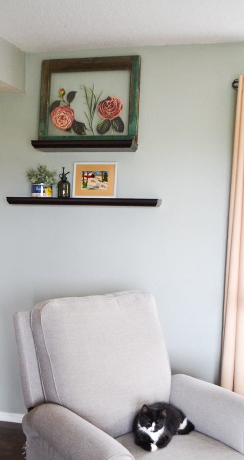 A zoomed out picture of an old window frame with flower transfers on it sitting on a shelf above a gray chair with a black and white kitten laying on the chair