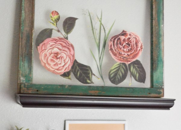 A chippy green window pane sitting on a shelf above another shelf with a small plant and picture frame