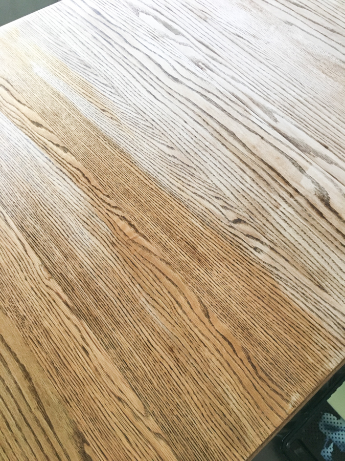 A close up picture of a tabletop that has half been sealed with a matte sealer and the other half is raw wood