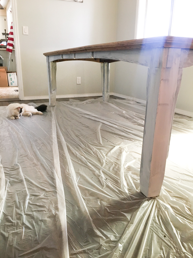 A side shot of a dining room table with a coat of white paint on the legs and a piece of plastic sheeting underneath