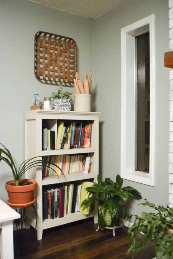 A chalk painted bookcase filled with books with green plants around it