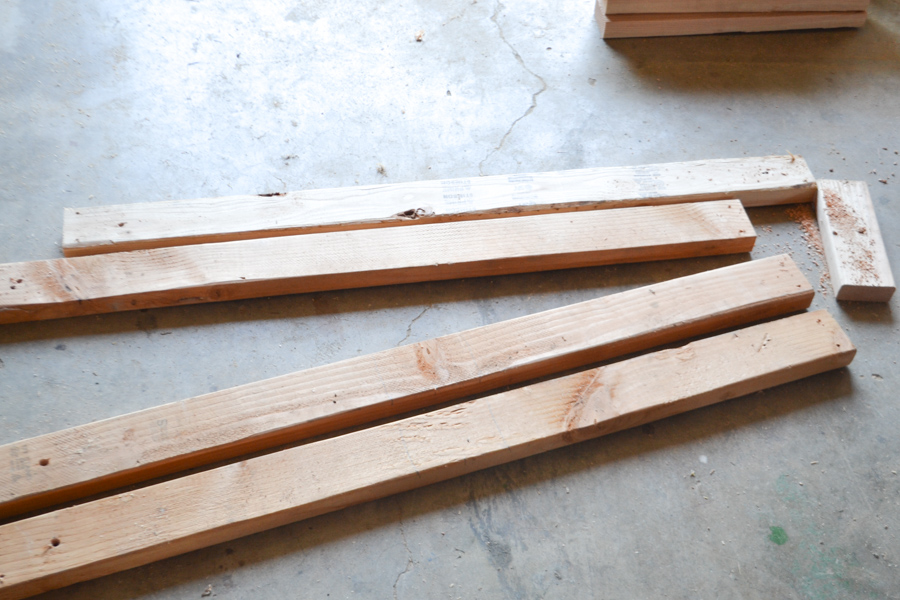 A pile of 2x4 boards laying on a concrete floor