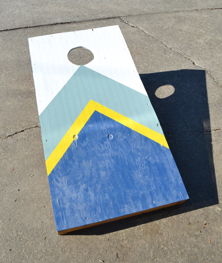 An above view of a striped painted cornhole board on a concrete driveway
