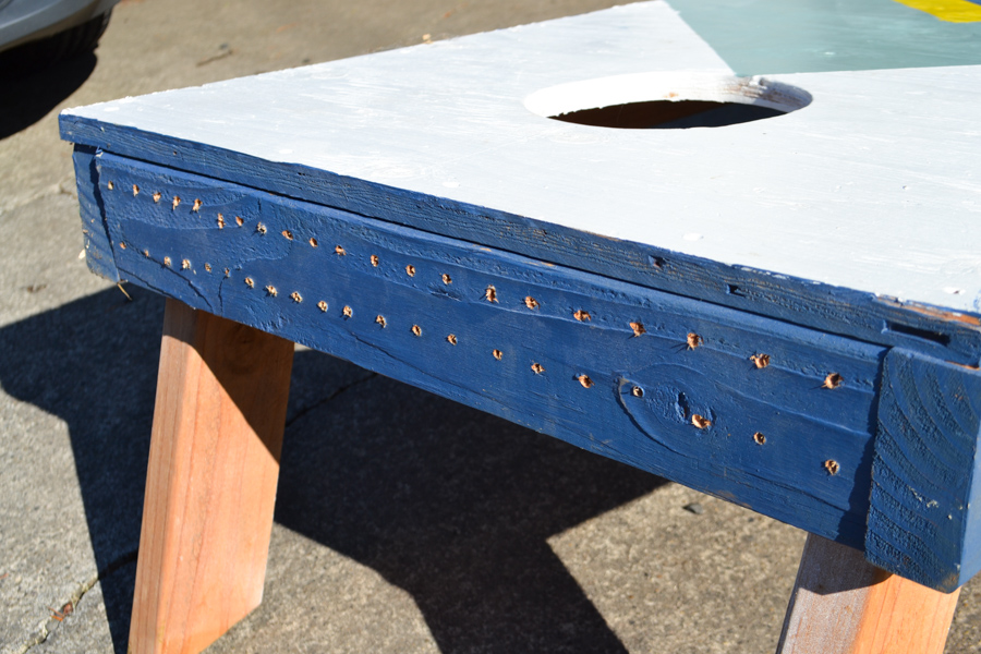 The back view of a cornhole board with screw holes drilled along the back