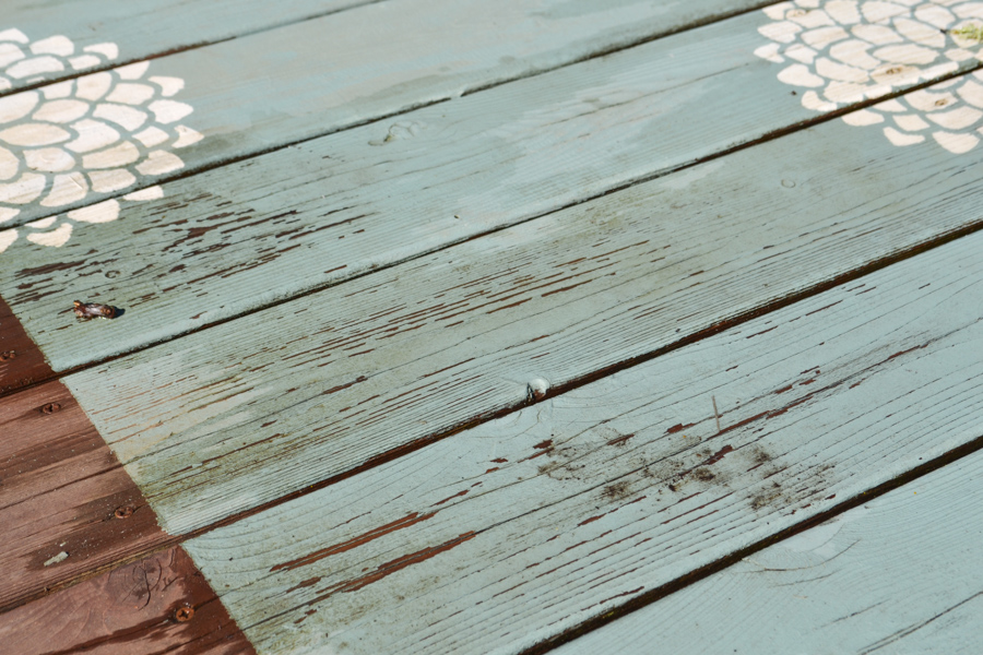 A close up of a dirty aqua painted deck rug