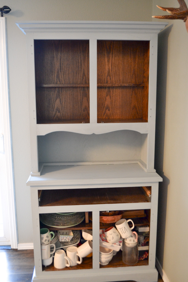 A full picture view of a china hutch with the most of it painted a gray blue