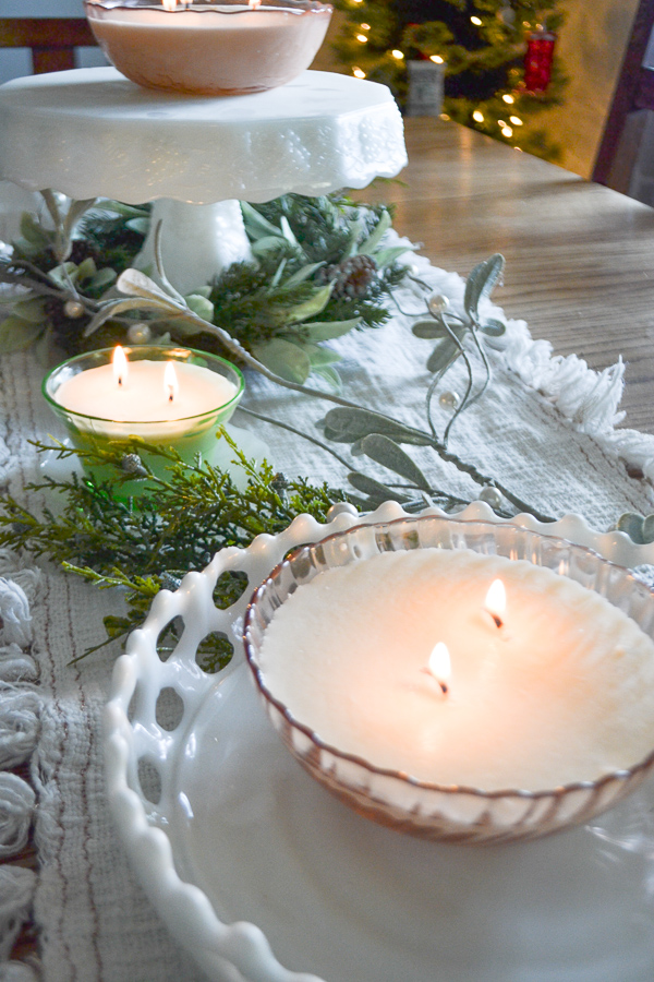 A close up of a pink depression glass soy wax candle in a white milk glass tray with faux Christmas greens