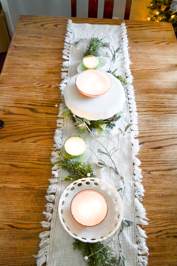 An above view of a soy candle lined table runner with faux Christmas greens