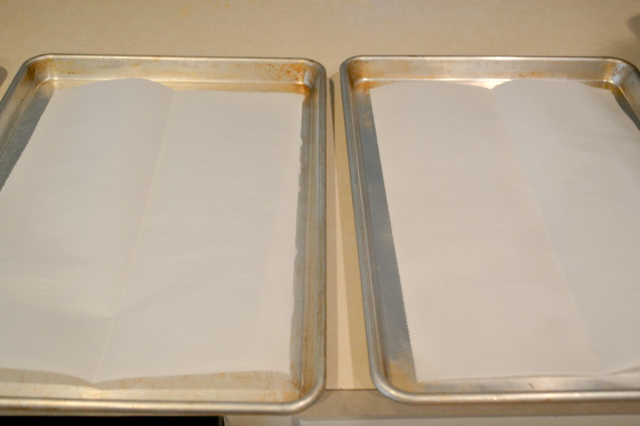 Two rimmed cookie trays with wax paper lining the bottom