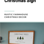 White, brown and green Christmas tree sign hanging over a bed with text overlay on the image